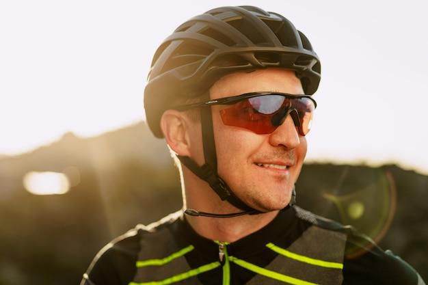 ヘルメットとメガネの男性白人サイクリストの肖像画をクローズアップ