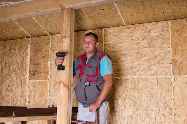 노출된 합판 파티클 보드가 있는 미완성된 집 안에 무선 드릴을 들고 있는 남성 건설 노동자 빌더의 초상화