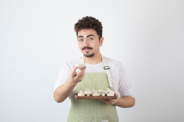 Портрет мужчины-повара, показаны сырые грибы на белом