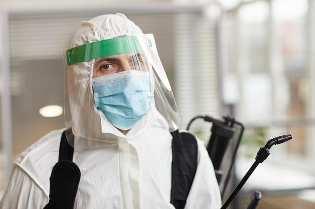 完全な保護具を身に着けて、オフィスを消毒しながらカメラを見ている男性の消毒労働者の肖像画、コピースペース