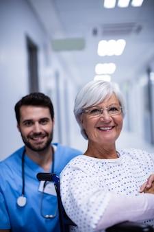 Портрет мужского доктора и женского старшего пациента, улыбаясь в коридоре