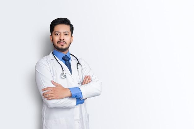 白い壁に分離された聴診器と腕の十字架を持つ男性医師の肖像画。健康保険の概念。
