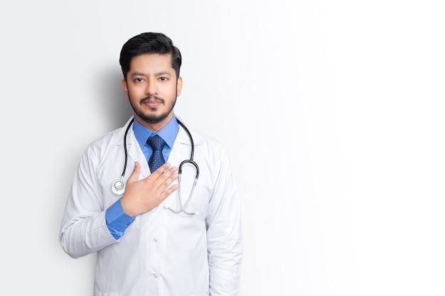 白い壁に隔離された胸に聴診器と腕を持つ男性医師の肖像画。健康保険の概念。