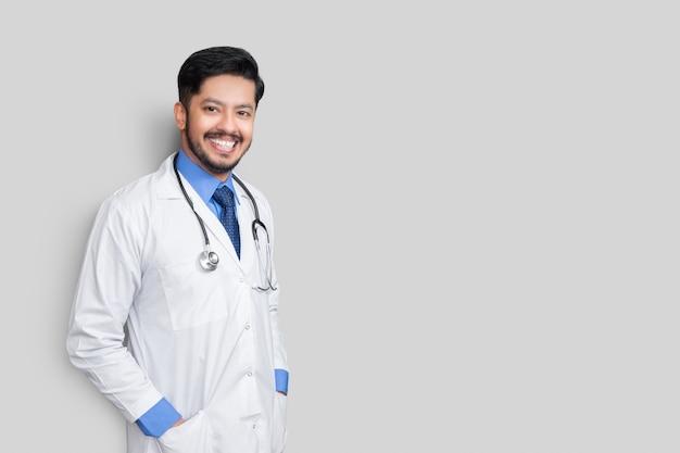 白い壁に隔離されたコートの聴診器と腕を持つ男性医師の肖像画。健康保険の概念。
