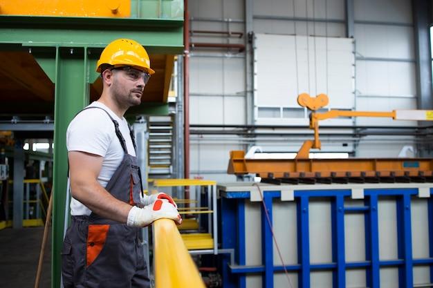 Портрет мужчины фабричного рабочего, опираясь на металлические перила в производственном цехе