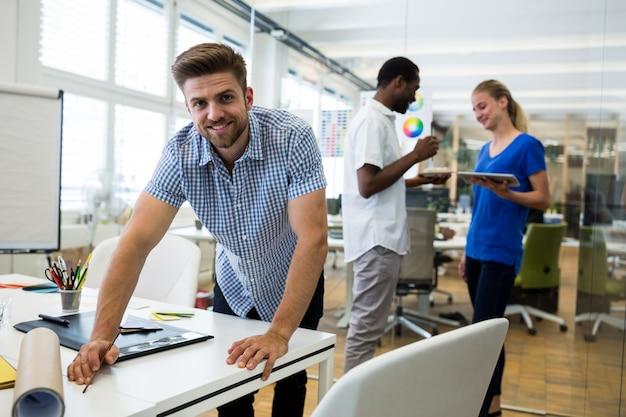 Портрет мужчины графического дизайнера, улыбаясь при взаимодействии с сотрудниками в фоновом режиме