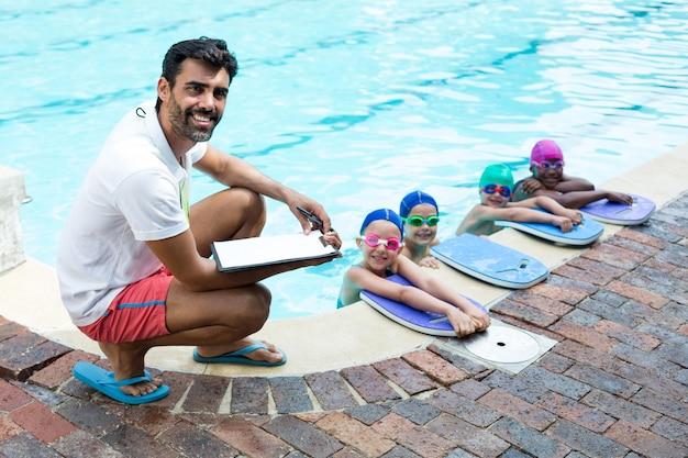 プールサイドで小さな水泳選手と男性インストラクターの肖像画
