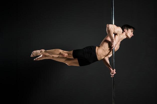 Портрет мужской модели, исполняющей танец на пилоне