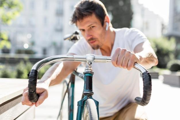 屋外で彼の自転車を修理する男性の肖像画