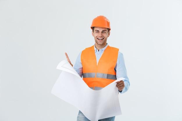 파란색 인쇄 용지를 들고 하드 모자와 남성 사이트 계약자 엔지니어의 초상화. 흰색 배경 위에 격리.