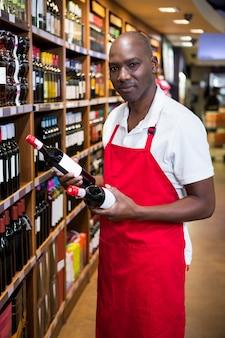 Портрет мужского персонала, расставляющий винные бутылки на полке