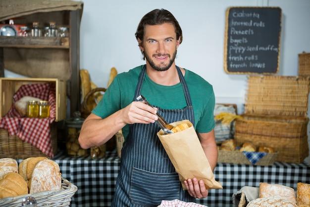 Портрет мужского персонала, упаковывающего хлеб в бумажный пакет