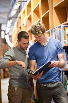 Портрет студентов-мужчин, глядя на книгу