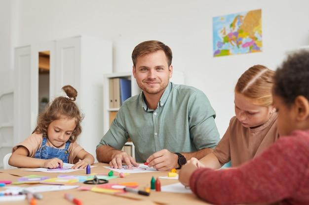 Портрет учителя-мужчины, улыбающегося во время работы с многоэтнической группой детей, рисующих картинки во время урока рисования в школе или центре развития