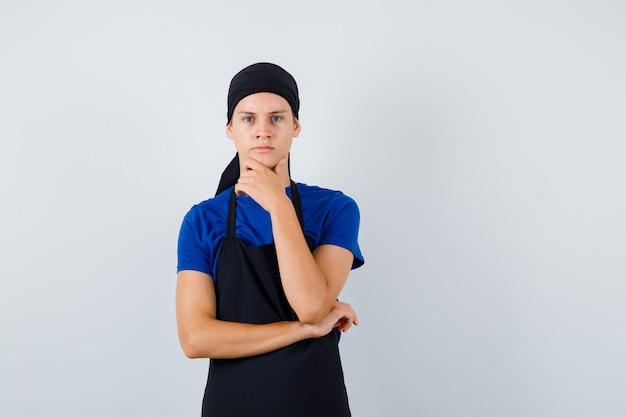 Портрет повара-подростка мужского пола, держащего руку за подбородок в футболке, фартуке и задумчивого вида спереди