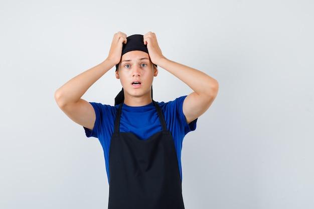 Портрет повара-подростка мужского пола, держащего руки за голову в футболке, фартуке и шокированного вида спереди