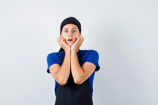 Портрет мужчины-подростка-повара с руками на щеках в футболке, фартуке и шокированным видом спереди