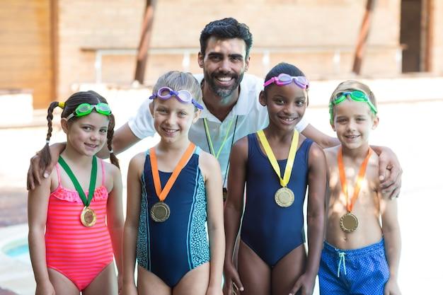 プールサイドで小さな水泳選手と男性トレーナーの肖像画