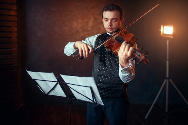 譜面台に対するバイオリンを持つ男性バイオリニストの肖像画。