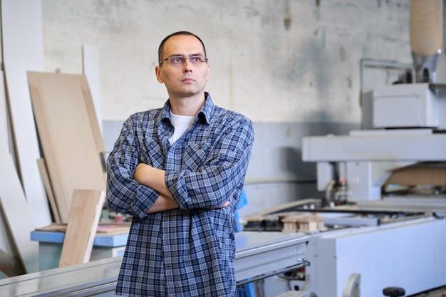 산업 생산에서 남성 노동자의 초상화입니다. 팔을 교차 캐주얼 셔츠에 안경 장갑에 자신감이 남자.