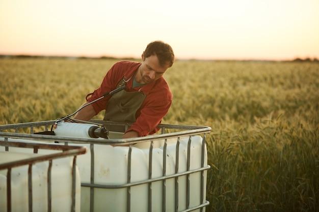 Портрет мужчины-работника, моющего инструменты и оборудование, стоя у резервуара для воды в поле на закате, копия пространства