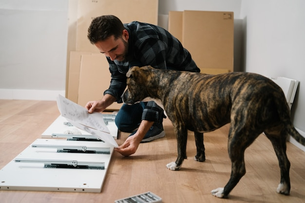 남자와 가구를 조립하는 그의 개 초상화. 가구 조립을 직접하십시오.