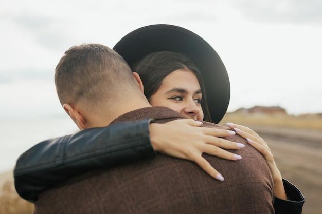 男性と女性の肖像画は屋外で抱き締めています