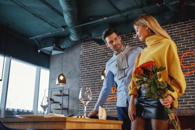 レストランに立っているカジュアルな服装の男性と女性の肖像画。女性はバラの花束を持っており、男性は席を提案しています。ロマンチックなディナーのコンセプト。横ショット