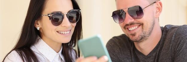 Портрет мужчины и женщины в солнцезащитных очках, сидящих в кафе и смотрящих в смартфон