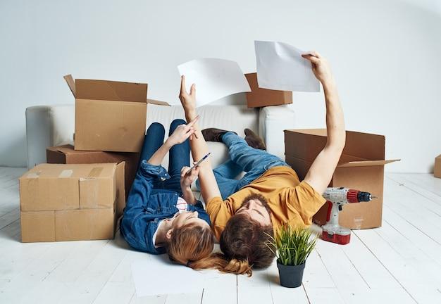 미래 아파트에 대한 계획을 움직이는 상자가있는 남녀의 초상화