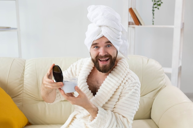 그의 얼굴 피부에 효과적인 크림을 바르는 남자의 초상화. 가정의 스파, 남성 개념을 위한 바디 및 스킨 케어.