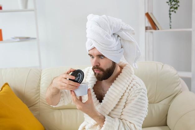 가정에서 얼굴 피부 스파에 효과적인 크림을 바르고 남성을 위한 피부 관리를 하는 남자의 초상화