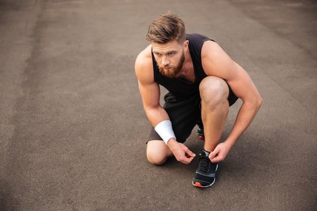 남자 운동 선수의 초상화 야외에서 그의 신발 끈을 묶습니다
