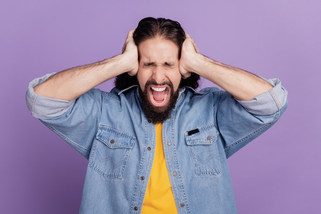 紫色の背景に男のカバー耳の肖像画は口を開けて悲鳴を上げる