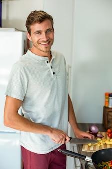 Портрет мужчины нарезка овощей на кухне у себя дома