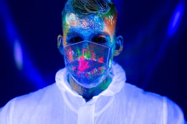 Портрет человека доктора в защитной одежде в ультрафиолетовом неоновом свете