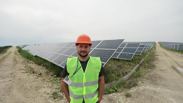 태양 전지 패널 필드에 서 있는 작업복에서 남자 엔지니어의 초상화. 청정 에너지 생산. 친환경 에너지. 생태 태양광 발전소.