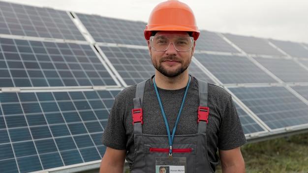 태양 전지 패널 분야에 서 있는 작업복에 남자 엔지니어의 초상화. 청정 에너지 생산. 친환경 에너지. 생태 태양광 발전소.