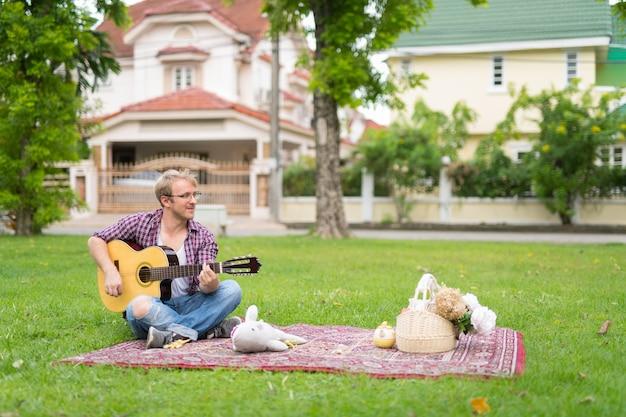 屋外でギターを弾きながらピクニックをしている男の肖像画