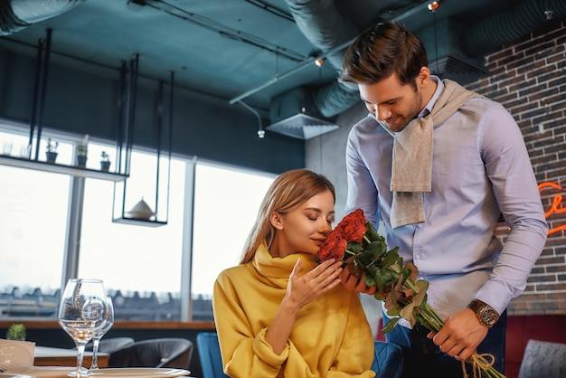 レストランに立っている間バラの花束を持っている男の肖像画。女性は花のにおいがします。ロマンチックなディナーのコンセプト。横ショット