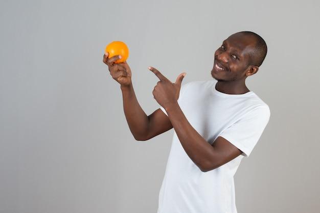 Портрет мужчины, держащего свежий апельсин на серой стене