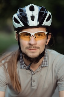 노란색 선글라스와 헬멧 도로에 자전거와 함께 서서 정면으로 보는 남자의 초상화