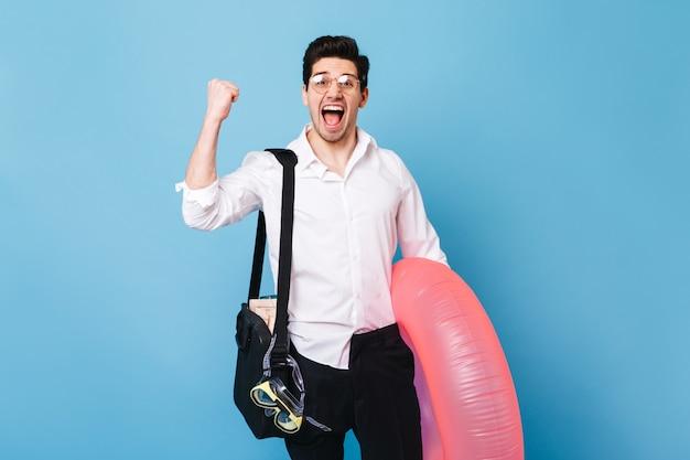 休暇の開始を楽しんでいるビジネス服の男の肖像画。青いスペースに対して膨脹可能な円でポーズをとる男。