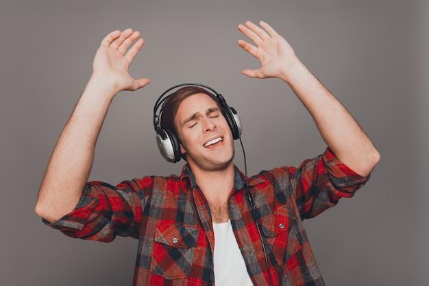 Портрет мужчины в кепке и наушниках, слушающего музыку и жестикулирующего с поднятыми руками