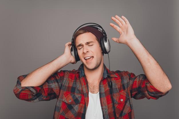 音楽を聴いて歌う帽子とヘッドフォンで男の肖像画