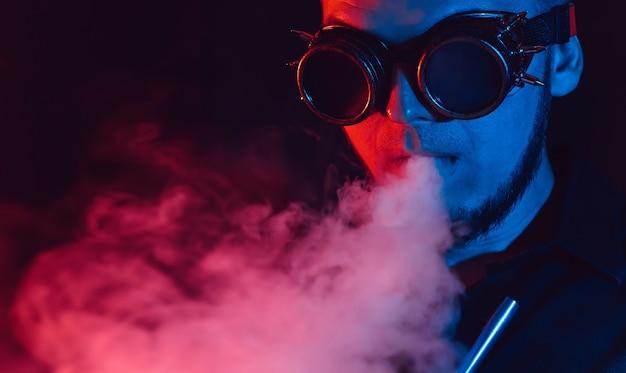 미래의 안경에 남자의 초상화는 물 담뱃대를 피우고 빨간색과 파란색 네온 불빛이있는 물 담배 바에서 연기 구름을 불어 넣습니다.