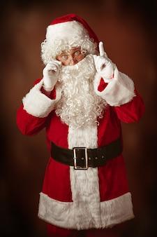 Портрет мужчины в костюме санта-клауса - с роскошной белой бородой, шляпой санта-клауса и красным костюмом на красном фоне студии