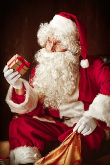 サンタクロースの衣装を着た男の肖像-豪華な白ひげ、サンタさんの帽子、贈り物と一緒に座っている赤いスタジオでの赤い衣装