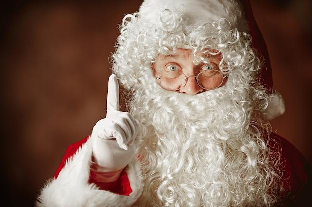 고급스러운 흰 수염, 산타의 모자와 빨간 의상을 입은 산타 클로스 의상을 입은 남자의 초상