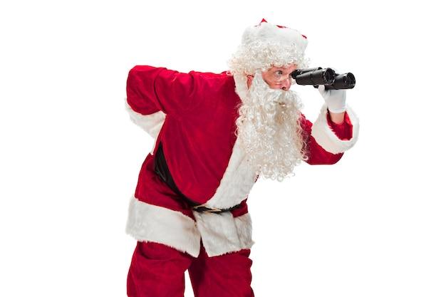 고급스러운 흰 수염, 산타의 모자와 빨간 의상으로 산타 클로스 의상을 입은 남자의 초상화-쌍안경으로 흰색에 고립 된 전체 길이